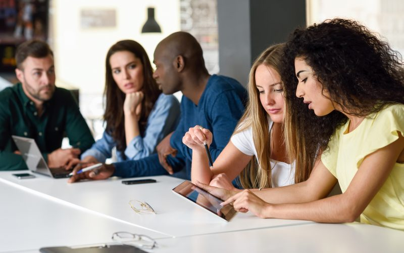 Five young people studying with tablet and laptop computer on white desk. Beautiful women and men working together wearing casual clothes. Multi-ethnic group.