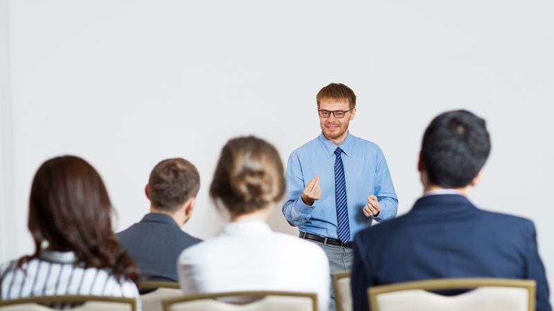 Smiling young businessman standing, gesturing and explaining something to sitting audience of four people. Rear view of audience.