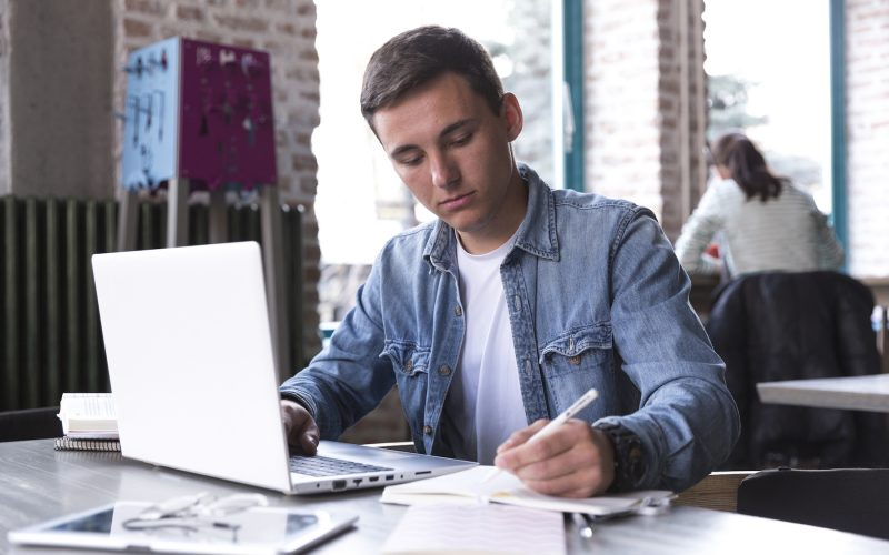Man at desk with laptop open writing on notepad next to him