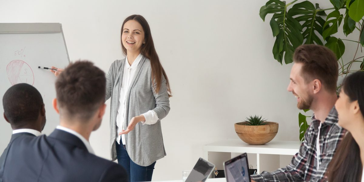 Lady at front of room teaching on white board with people sat at desk