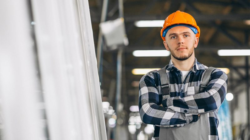Man in shirt and with orange hard hat in factory with arms crossed