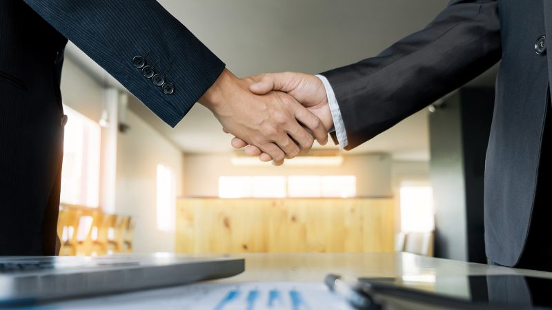Two men shaking hands over table