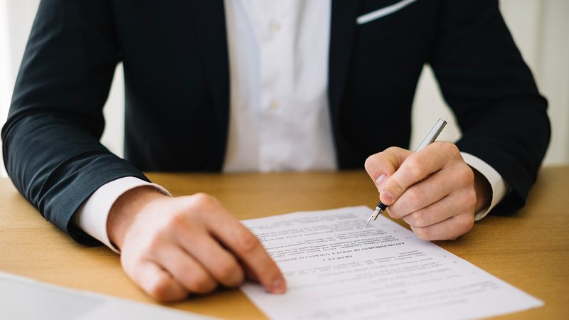 Man in suit with pen signing document