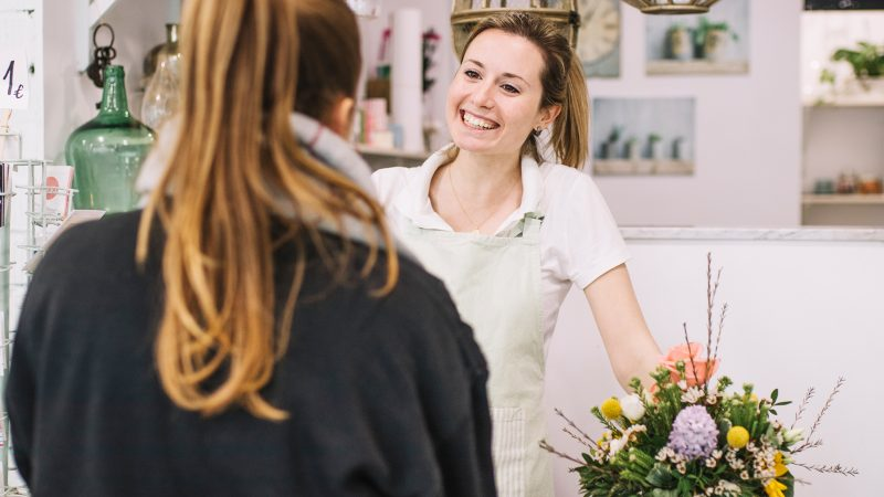 Lady in shop smiling and serving a customer