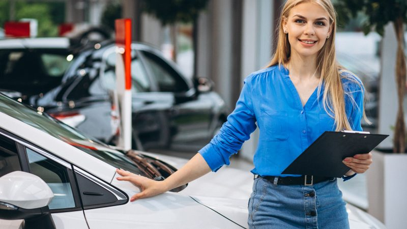 Sales lady with clipboard smiling next to car