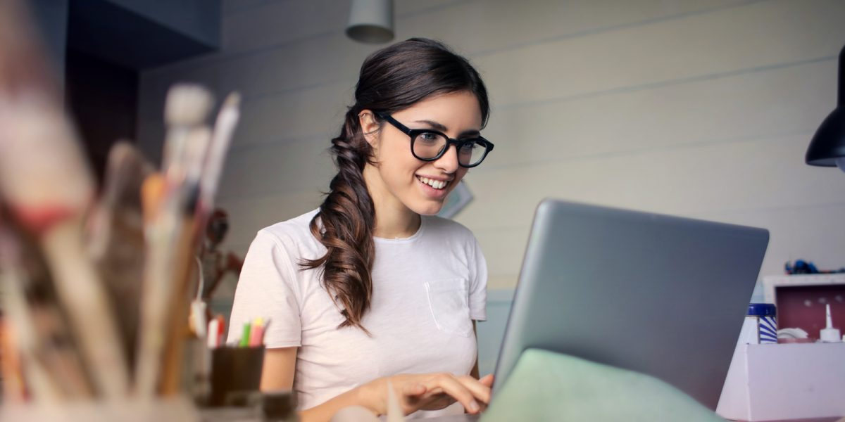 Lady in glasses looking at laptop working and smiling