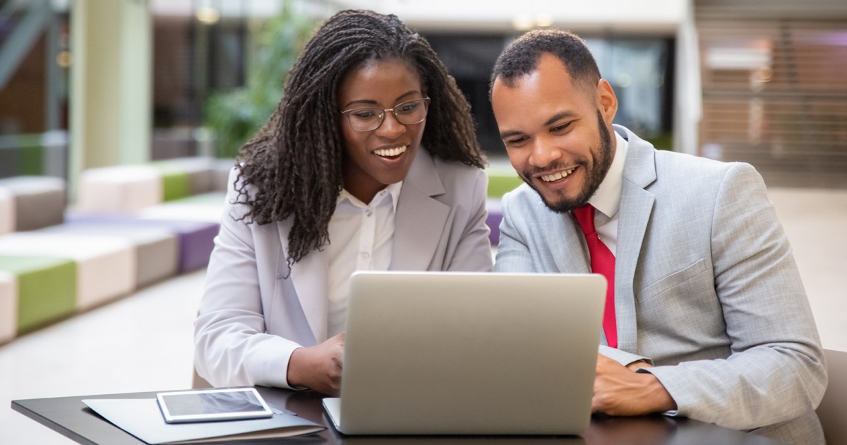 Man and woman sat at desk on laptop smiling in suits